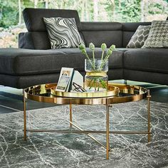 Get a luxe living room look with the round gold Genesis table.