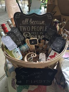 """A basket of Firsts- wedding or bridal shower. The basket, """"All because two people fell in love"""" sign, the chalk asked and the small burlap heart and cross and the letter """"C"""", wine stopper and bookmark all from Hobby Lobby.  Iordered the signs for the bottles off of Etsy. Wine is from Walmart.  For first fight- mad housewife wine.  Wedding night- champagne. First anniversary - milestone wine.  First baby-lucky duck wine Housewarming party-sutter home.  Honeymoon- naked grape wine"""