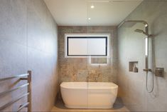 This bathroom design uses tiles behind the bath for a fantastic feature in the guest bathroom of this architectural home. . Build by FERGUSON BUILDERS, QUEENSTOWN. . #bathroom #tiles #bathroomdesign #tiledfeaturewall Drinks Cabinet, Ceiling Beams, Man Cave, Tiles, New Homes, Design Inspiration, Bathroom, Architecture, Big