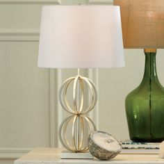 Wellington Table Lamp | This airy table lamp features a silver finish over its steel construction. It is complemented by an off-white colored hardback drum shade.