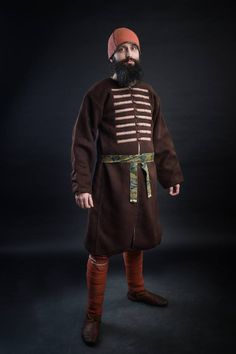 """A rich merchant from Birka, the middle of X century """"Kaftan"""" sewn of thick diamond twill decorated with pattern-woven silk bands and possaments of type P10. Silk belt with silver possaments (type P20) Woolen troussers dyed with madder and madder-dyed leggings Woolen cap decorated with thin bands of silk."""