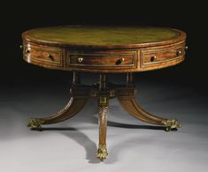 A FINE REGENCY GILT-BRASS-MOUNTEDPART-EBONIZEDMAHOGANY, EBONYAND KINGWOOD LIBRARY DRUM TABLE  CIRCA 1810 The circular drum top fitted with a gilt-tooled green leather lining withing a kingwood cross-banding, the conforming frieze fitted with four drawers alternating with four swinging triangular-shaped doors, raised on four turned columns on a quatripartite plinth fitted with squared ormolu flowerheads and raised on downswept legs carved with acanthus leaves