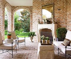 Taking a cue from the architecture of the house, this shapely fireplace surround creates an elegant focal point for this covered patio. The mantel offers prominent display space for a collection of small sculptures. A large painting hung above the mantel creates a unique style statement that's not often featured in outdoor rooms./