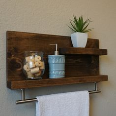 Handmade 2 tier bathroom shelf with satin nickel towel bar. The perfect addition to any home bathroom, apartment, or condo. Made from solid wood. It has been lightly sanded down, then stained and sealed with a beautiful dark walnut finish. This piece does not include the accessory items as shown in the pictures. The color of the stained wood captured in the photos might vary slightly. Dimensions: 23 in wide x 11 in tall x 4/6 in deep (top shelf 3.5 in dp x 12 in lg, lower shelf 3.5/5.5 in...