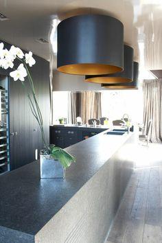 pland de travail de cuisine en pierre , grosse suspension noir et or , orchidée