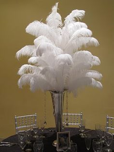 Great example of a DIY centerpiece, Simple and elegant polished Silver #TrumpetVase with feathers and hanging crystal strands. To add an extra bit of elegance, dye your white ostrich feathers to match your event.