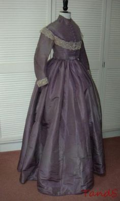 Purple silk day dress, trimmed on yoke and cuffs with Bedfordshire bobin lace; narrow stand up collar, lined in white cotton sateen; dark blue velevet ribbon trim on  yoke; decorative fabric buttons; coat sleeves; skirt seems to be detached from original waistband or bodice; skirt lined with cotton,