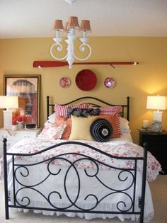 Black iron bed, night stand; black/white pillows; white duvet, lamps, and chandelier; red/white pillows, quilt, chandelier lampshades, and wall accessories; and buttery yellow walls ... this bedroom just makes me smile :)