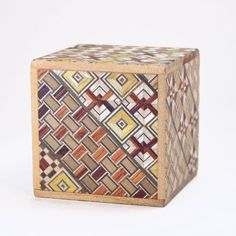 This little guy is a four step puzzle box handmade in Japan by Hiroyuki Oka. What makes it a puzzle box? To open this wooden box you must follow a sequence of four steps, sliding the panels just a bit