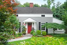This vintage house looks much the same as it did 82 years ago, but with gray paint on the original cedar shakes, a berry-red door, and lush plantings.