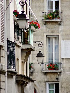 Tall narrow French windows in Paris  open up to a small balcony decorated with flowering plants, overlooking the street below!