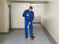 A Prestige Property Service team member wearing his standard commercial cleaning services blue jumpsuit, sweeping the floor of an office building.