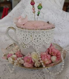 teacup pincushion - may like this one better, at least i like the lace around the rim (maybe use narrower? maybe not) and the silk flowers and pearls around the saucer. so pretty! with the lace, it wouldn't matter so much to find the perfect painted teacup design