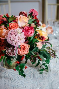 Centerpiece designed in a gold compote in peaches, corals, and pinks
