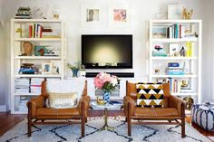 I love this shot by @emilyhenderson because people think they have to clear the whole entire space in front of a TV, but than it really makes the focus solely on the TV in the room.  These low profile chairs are perfect! Great fo when TV is off and totally not in the way when it's on #Livingroomdecor #whattodowiththeTVintheroom