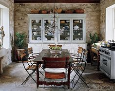 Crystal chandelier in a rustic kitchen with farm table, French bistro chairs, stone walls and floor!  Wow!