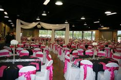 This wedding reception used black table cloths, black and white table runners, hot pink napkins and white chair covers with hot pink bows. They also added white fabric on the ceiling coming out from a chandelier.