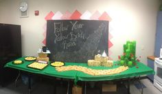 """Decor on the other side of the room. On the large chalkboard I wrote a different Wizard of Oz movie quote for each day. Each day also had a corresponding gift / theme. Day 1 (Monday) was """"Follow your yellow brick road"""" We made a yellow brick road of Twinkies, leading up to our table top Emerald City. Also their is the spiral part yellow brick road on the other end with Rice Crispy treats on a red circle plate in a spiral design. And for something a little less sweet there is poppy seed…"""