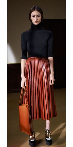Fall 2013 Céline: BLACK CASHMERE TURTLENECK SWEATER; CHOCOLATE PLONGÉ PLEATED SKIRT;  SINGLE SHOPPER IN VEGETAL CALFSKIN.