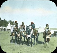 "Early 1900's Notes 	Four Crow women on horses with beaded martingales, three women wearing elk tooth dresses for parade in Montana. Tipis in background.  Hand written on edge of slide, ""Montana - Crow Squaws with their elk tooth dresses."""