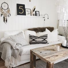 neutral living room | rustic modern wood coffee table | layers of blankets + pillows | floating wood shelf & metal typography
