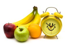 Bananas apples and oranges with a happy face clock on a white background bananas