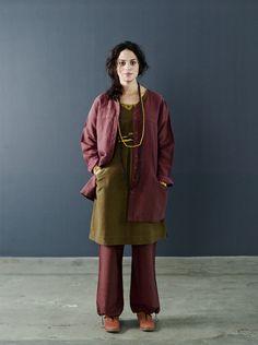 Herbstmode Basics 2012 - Jacke in Kastanie:  Die Baumwolljacke hat eine leichte A-Form mit Schulterpasse und zwei geräumige Taschen. Kombiniert ist sie mit einem eukalyptusfarbenen Kleid, dem Langarmoberteil 'Vippa', einer Hose aus Leinen und dem borkefarbenen Schal 'Sigal', der um die Taille gebunden ist.