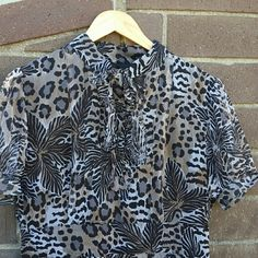 """SALE 🚀 Leopard Print Silk Dress NWOT Cute and flirty leopard print dress with many cute details. Buttons and ruffles on the front with bow on top. Sleeves also have buttons. Zippered side. 100% silk shell and 100% polyester shell. Never been worn and in excellent condition. Only flaw is the minor snag in the upper back - photo 4. Not noticeable but price has been adjusted for this. About 15"""" across at waist with no stretch and about 36"""" from top of shoulder to hem.  No trades, holds, or…"""