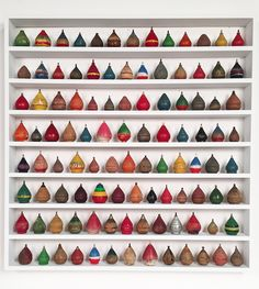 """ollection of 104 antique wooden spinning tops in different shapes, sizes and colors. Mounted in a custom made white painted maple shadow box measuring 30"""" x 31"""" x 21/2"""" Price on request"""