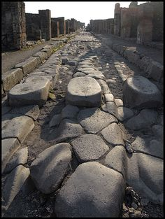 Stepping stones in Pompeii. This allowed people to walk across the road and not get their clothes besmirched by muck. The gaps between the stones is to allow for wagon wheels to go by. Pompeii Ruins, Pompeii Italy, Pompeii And Herculaneum, Ancient Ruins, Ancient Rome, Ancient History, Roman Roads, Empire Romain, Roman City