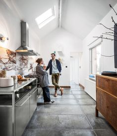 For the new kitchen, they incorporated a Smeg cooktop, oven, and range hood, stainless steel cabinets from Habitat, and personal accessories like a prototype goblet.  Photo by Tim Van de Velde.