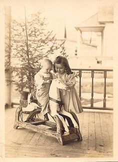 Two darling Edwardian siblings enjoy a moment of fun on their family's front porch with a wooden rocking horse at the center of their merriment.