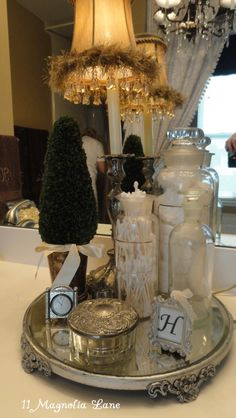 Bathroom Storage Display - collected bottles and silver are used to create decorative storage - via 11 Magnolia Lane