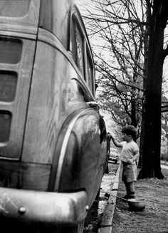 Gordon Parks: Happy little boy assisting with washing the car. 1953