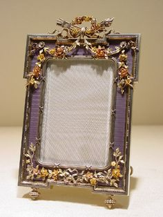 A coloured gold mounted guilloché enamelled silver gilt photograph frame by Fabergé, of rectangular form with translucent mauve enamel over a waved guillochage, mounted with four-coloured gold floral trails and festoons, centred by a chased silver reed bezel tied with bows suspended from a chased flame and quiver surmount encircled by a floral gold wreath. Workmaster: Johann Victor Aarne, St. Petersburg, pre-1896.