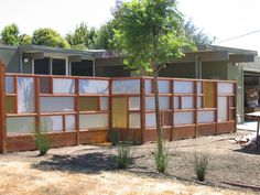 irregular patchwork fence from salvage. i love the midcentury look of the layout.