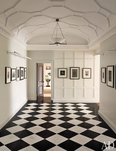Iconic photographs of New York greet visitors in the foyer of this historic Manhattan apartment, which was renovated and furnished by Shelton, Mindel & Assoc.; the plasterwork ceiling and the picture lights were designed by the firm.