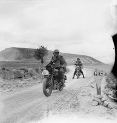 Motorcycle despatch riders wearing gas masks during a section of a 50-mile motorcycle trial in Cyprus, 3 March 1942.