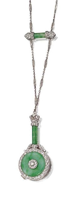 JADE AND DIAMOND LORGNETTE AND CHAIN, CIRCA 1920.  The hinged spectacles contained within a case set with a disc of apple green jade, the handle composed of a jade cylinder, set with 59 old European-cut diamonds weighing approximately 6.50 carats, mounted in platinum, signed N, supported on a platinum chain of fancy links decorated with another jade cylinder, the terminals set with single-cut diamonds, length approximately 33 inches.