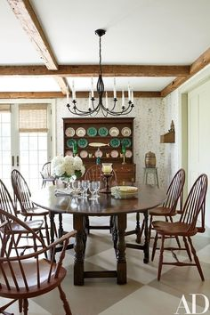 A contemporary oak dining table is paired with Windsor chairs from Nantucket House in the family room | archdigest.com
