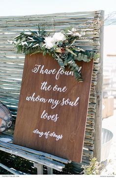 A biblical quote, printed in a feminine font, was displayed on a wooden board embellished with a composition of eucalyptus leaves. | Photographer: Yolandé Marx | Florist: Studio Bloem