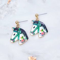 Cute floral horse head charm earrings.These unique coloured horse head earrings would make a great gift for your loved one with a passion for horses. The earrings are a drop style with butterfly back and gold plated finish. Your order will arrive enclosed in an ivory organza gift bag ready for you to gift your loved one.Gold tone alloy and coloured resin.Horse charm measures approx 2.1 cm x 3.4 cm.