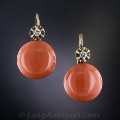 A beautiful matched pair of rich orange salmon colored coral buttons, measuring just over 1/2 inch diameter, each crowned with a single diamond sparkler, compose these classic early-20th century vintage earrings hand fabricated in in 14K yellow gold (and white gold for the diamond settings). 7/8 by 1/2 inch.