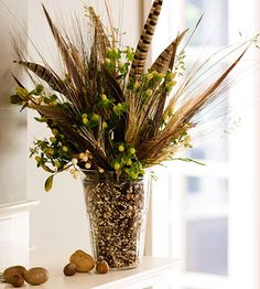 Create a simple bouquet inspired by nature with feathers, wheat, and nuts. Place it on a mantel, coffee table, or dining table for a creative focal point. Fill a vase with nuts or seeds, leaving enough room to arrange the feathers and wheat. Accent the arrangement with greenery.