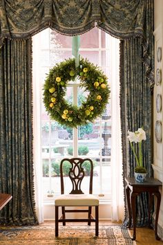 An overscale wreath is dotted with edible treats--apples, lemons, and nuts--as well as Hypericum berries and osage oranges. Barry Dixon