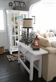 Fox Hollow Cottage Christmas Holiday Home Tour. Chunky rustic console table with cozy cabin lanterns and snow dusted mini trees. Farmhouse cabinet with vintage style FROSTY the Snowman appearance announcement from #homegoods www.foxhollowcottage.com sponsored pin
