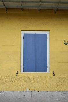 Bright yellow creole cottage with cornflower blue shutters in the Quarter Shutter Colors, Shutter Decor, Garage Paint Colors, Paint Colors For Home, New Orleans Architecture, Shutter Designs, Creole Cottage, Outside Paint, Blue Shutters