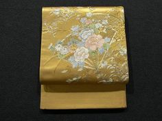 This is a graceful Fukuro obi with beautiful seasonal flowers on folding fan motifs, which are embroidered on the brilliant gold background.