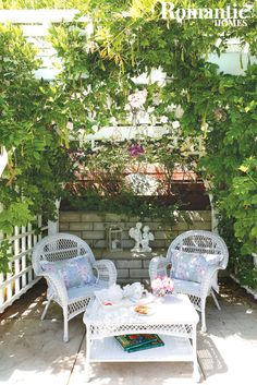 Garden grotto with white wicker chairs and table