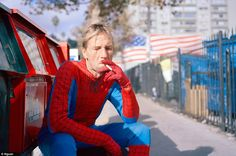 Smoke break: A man who doesn't bear much resemblance to Spiderman apart from his suit takes five minutes off being a superhero